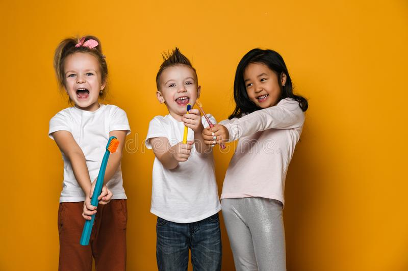 Dental hygiene. happy little cute children with toothbrushes. stock photos