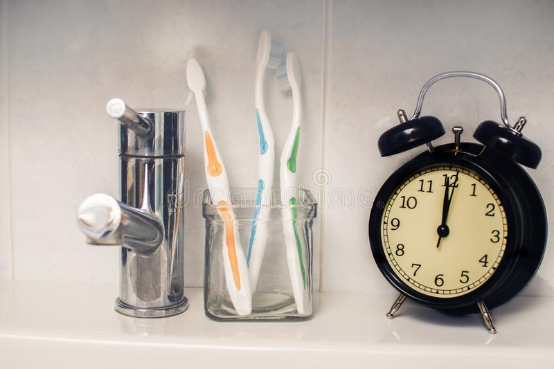 Dental hygiene time concept. Black alarm clock in the washroom next to toothbrushes stock image