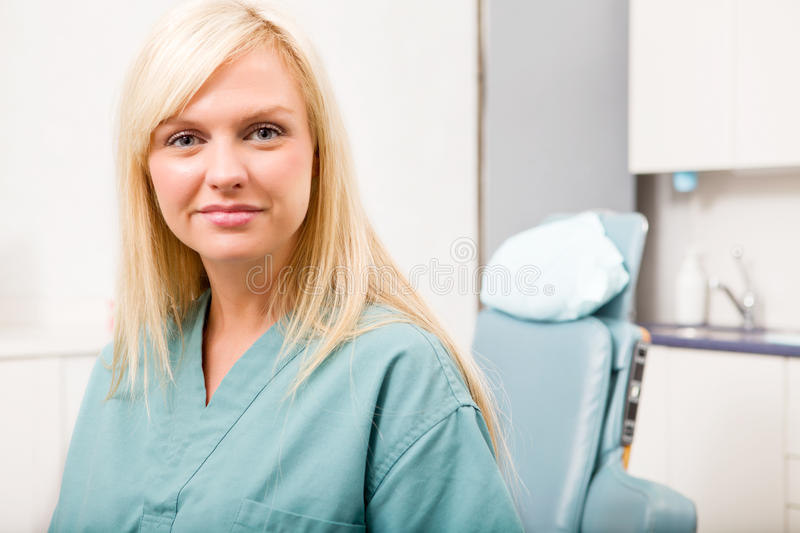 Dental Hygienist. A portrait of a dental hygienist in front of a dental chair stock photo