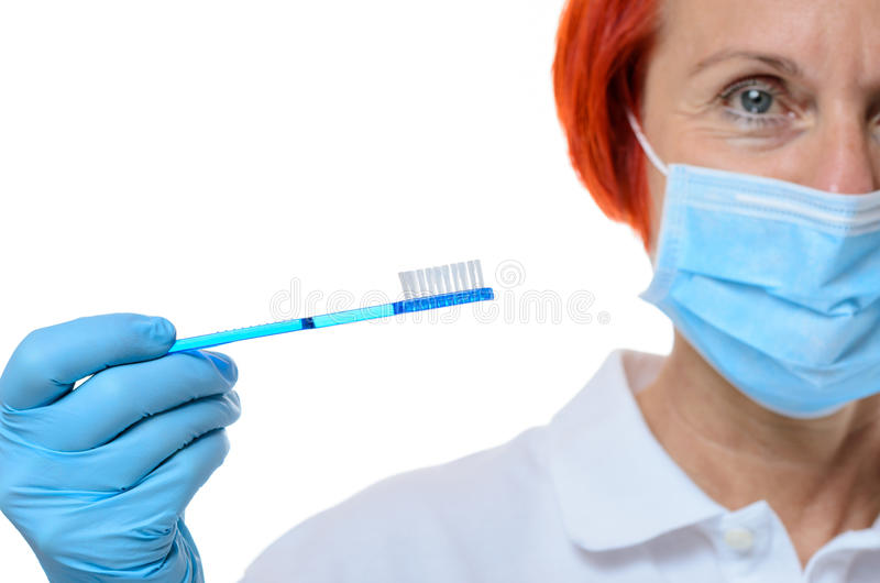 Dental hygienist in red hair with toothbrush. Single dental hygienist in red hair with face mask and toothbrush in hand over white background royalty free stock photo
