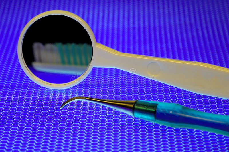 Dental Instruments. Dental Mirror and Probe on Blue Textured Background royalty free stock photography