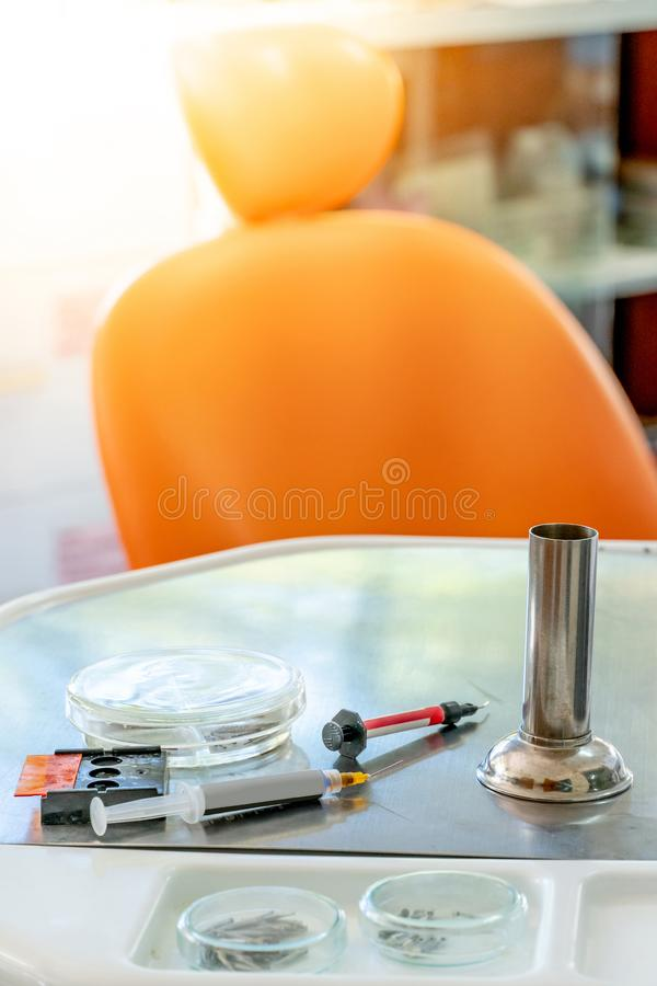 Dental instruments and medical supplies in clinic. Dental instruments and medical supplies on metal tray in the clinic. Empty orange dental chair and tools for stock photos