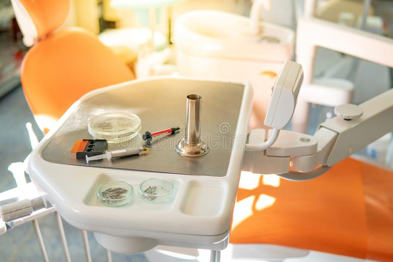Dental instruments and medical supplies in clinic. Dental instruments and medical supplies on metal tray in the clinic. Empty orange dental chair and tools for royalty free stock image