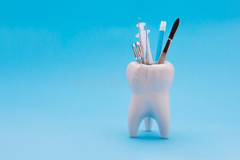 Dental instruments mirror a probe a tweezers syringe stand in a. Ceramic model of a human tooth. Copy space with use as background under the inscription stock image