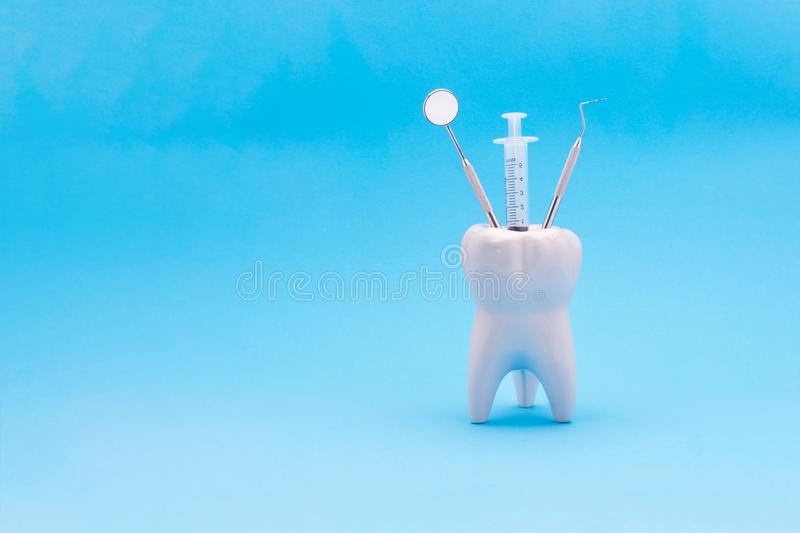 Dental instruments mirror a probe a tweezers syringe stand in a. Ceramic model of a human tooth. Copy space with use as background under the inscription stock photo