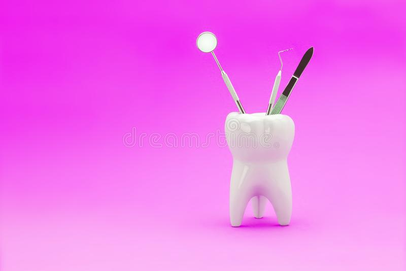 Dental instruments mirror a probe a tweezers syringe stand in a. Ceramic model of a human tooth. Copy space with use as background under the inscription stock images