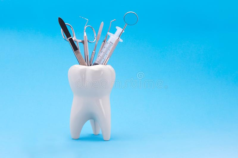 Dental instruments mirror a probe a tweezers syringe stand in a. Ceramic model of a human tooth. Copy space with use as background under the inscription royalty free stock image
