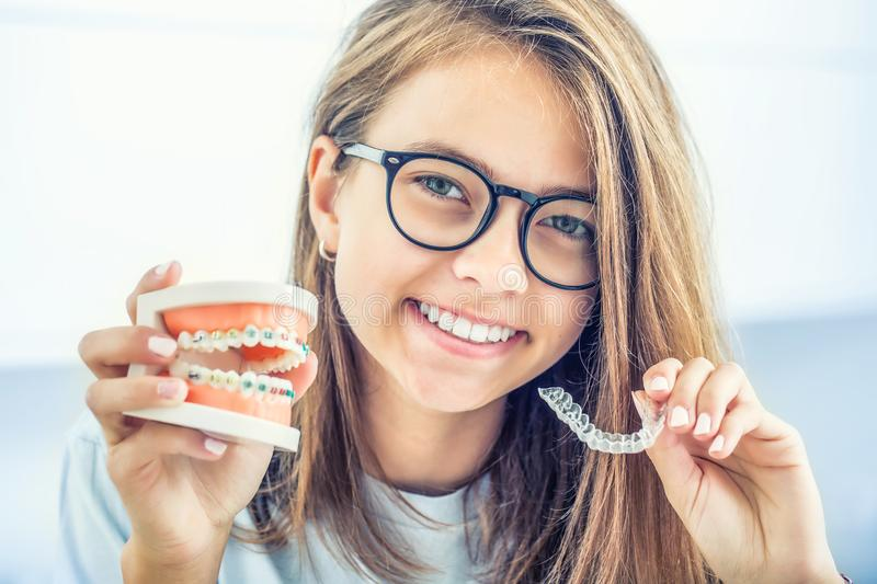 Dental invisible braces or silicone trainer in the hands of a young smiling girl. Orthodontic concept - Invisalign stock images