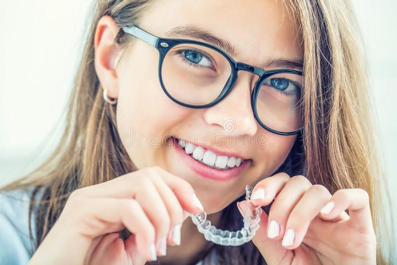 Dental invisible braces or silicone trainer in the hands of a young smiling girl. Orthodontic concept - Invisalign royalty free stock photo