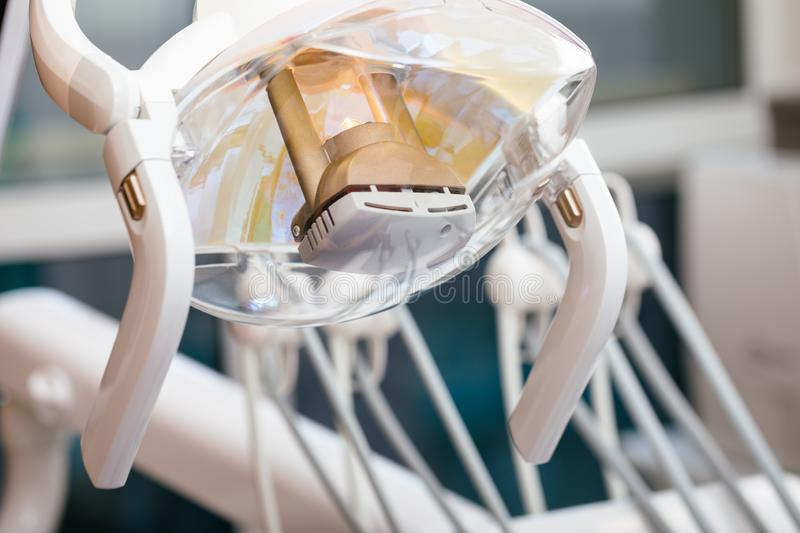 Dental lamp in dental clinic close-up. Close-up shot of illuminated electric dental lamp with handles, a part of dental engine, pediatric dental clinic royalty free stock photography