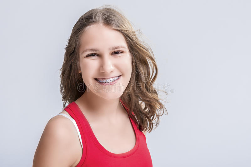Dental and Medical Concept. Smiling Caucasian Young Blond Teenage Girl With Teeth Bracket System. Against White Background. stock photography