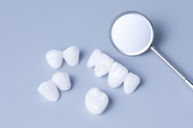 Dental mirror and dentures on a light blue background. Zirconia dentures is used for cosmetic purposes in dental clinics stock photography