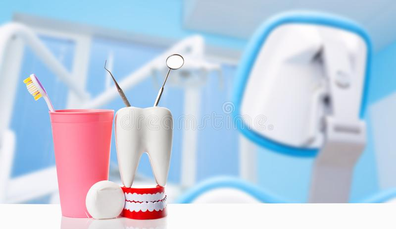 Dental mirror and dental explorer instrument in white tooth model, human jaw and dental floss near toothbrush in pink glass. Against dental office background stock images