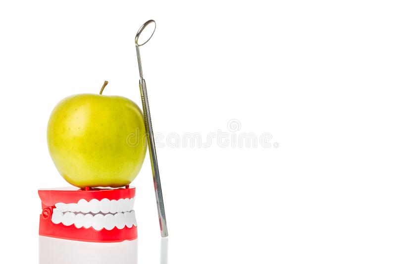 Dental mirror near green apple on human jaw model isolated on white. Oral dental hygiene. Free space.  royalty free stock photography