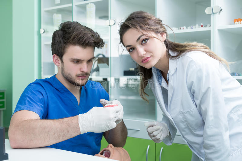 Dental prosthesis, dentures, prosthetics work. Prosthetics hands while working on the denture, false teeth, a study and a table wi. Th dental tools stock photo