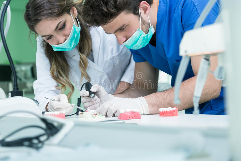 Dental prosthesis, dentures, prosthetics work. Prosthetics hands while working on the denture, false teeth, a study and a table wi. Th dental tools stock photos