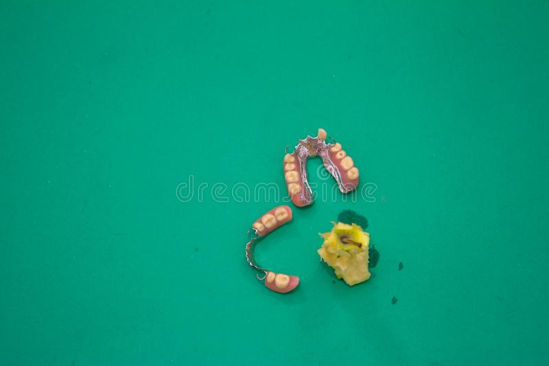 Dental prosthesis in motion eating a apple stock photos