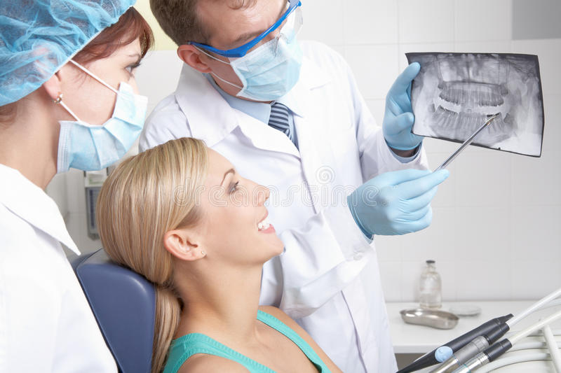Dental x-ray. A dentist showing a patient her teeth x-ray royalty free stock images