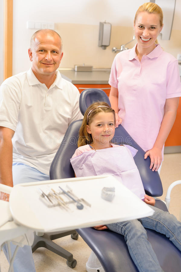Dental team in stomatology clinic with child. Portrait of dental team with young girl in stomatology clinic royalty free stock photo