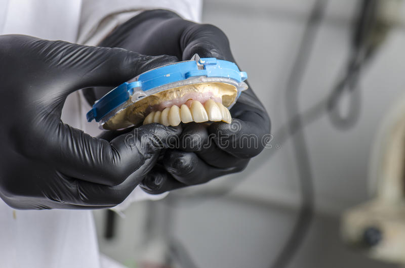 Dental technician holding a monolithic zirconia. Restorations full arch implant supported with the ceramic load in vestibular royalty free stock photography