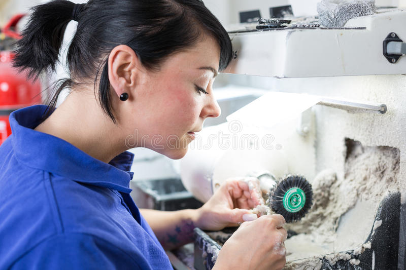 Dental technician polishing a prosthesis. In a laboratory royalty free stock images
