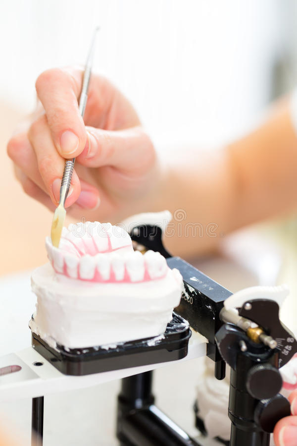 Dental technician producing denture stock photos