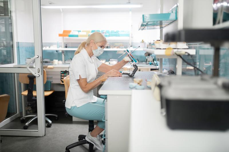 Dental technician working on cast model of teeth. Prosthetic technician. Concentrated dental technician wearing mask sitting at her table working on cast model royalty free stock image