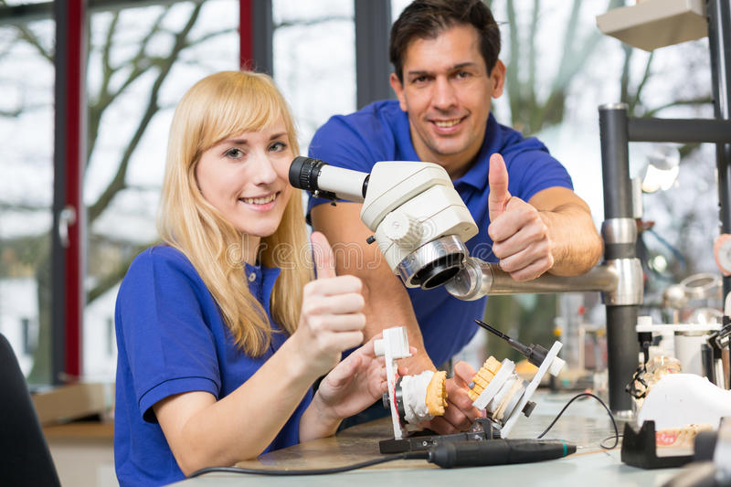 Dental technicians showing thumbs up. Dental technicians working at a microscope showing thumbs up royalty free stock photos