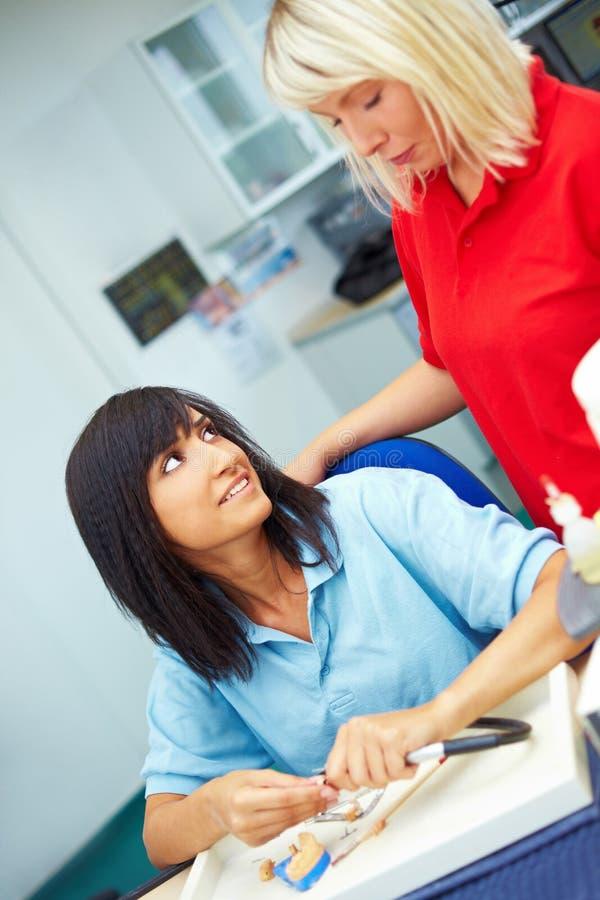 Dental technicians talking. Two female dental technicians talking in laboratory royalty free stock images
