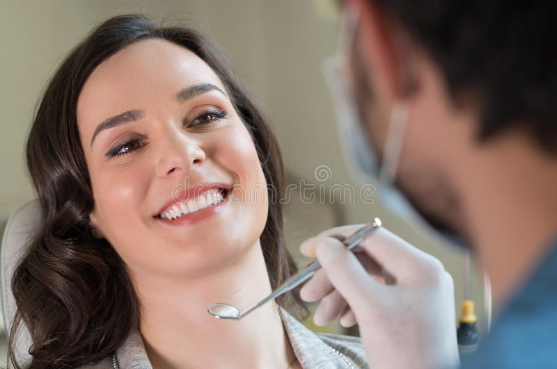 Dental treatment. Closeup of dentist visiting a patient in clinic royalty free stock photography
