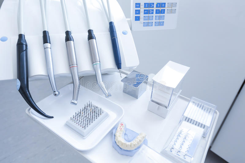 Dental treatment tools with nozzles. Dental practice - specialist tools, drills, handpieces and laser with polish nozzles, drill nozzles and denture model in the stock photos
