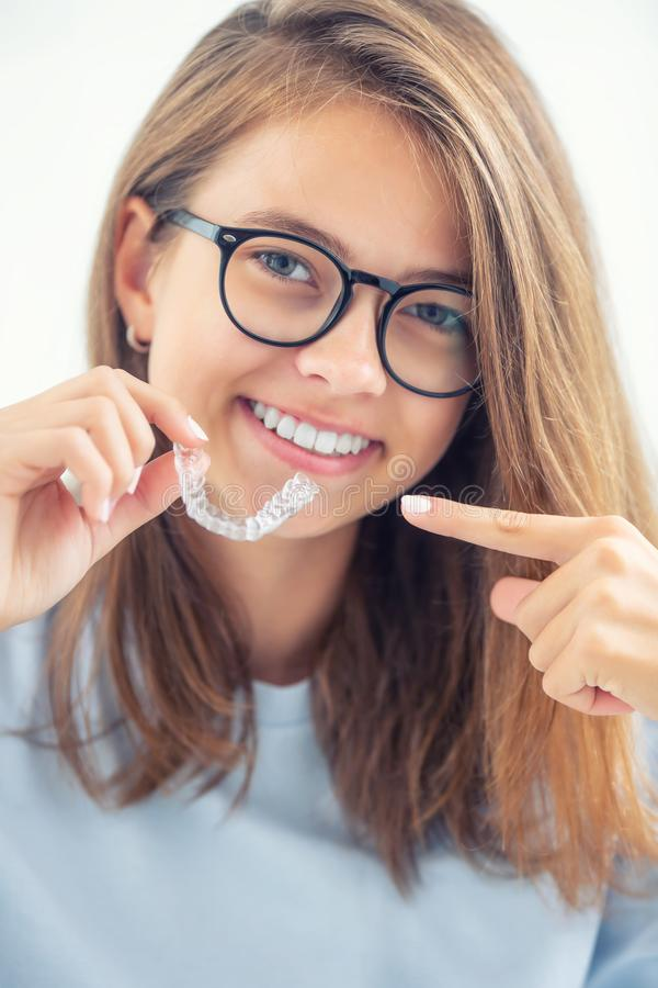 Dentale onzichtbare steunen of siliconentrainer in de handen van een jong glimlachend meisje Orthodontisch concept - Invisalign stock foto's