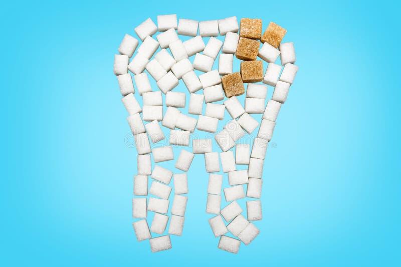 Dente de cubos do açúcar com cáries na frente do fundo azul imagem de stock