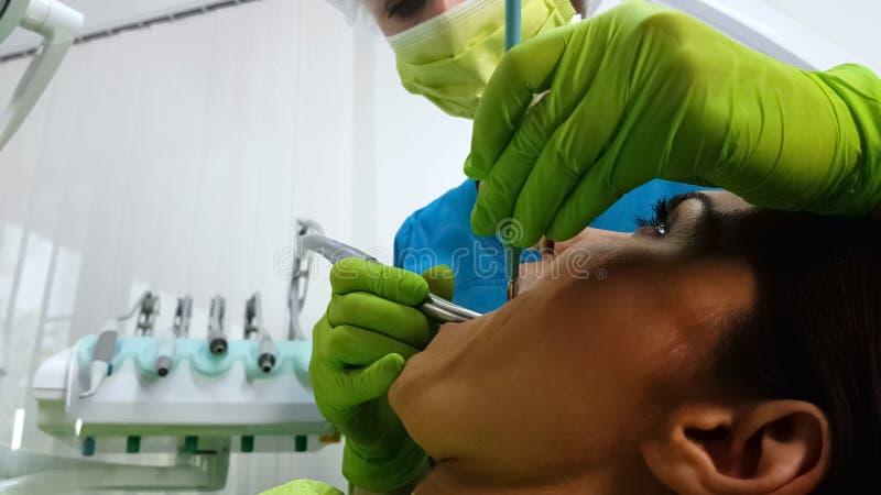 Dente de furo qualificado dos pacientes da senhora do dentista, removendo a cárie, serviços dentais imagem de stock