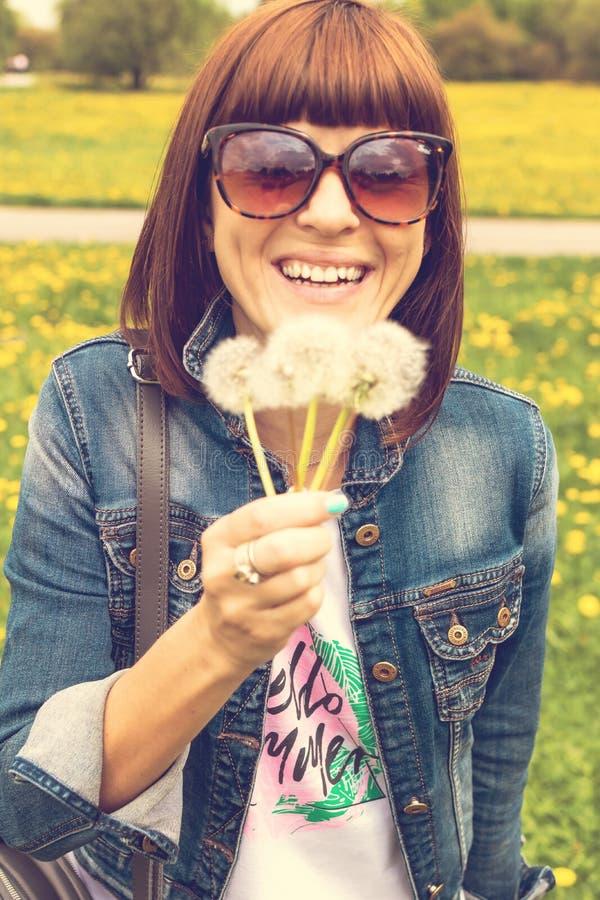 Dente-de-le?o de sopro da menina bonita no parque do ver?o Natureza bonita da grama verde imagens de stock