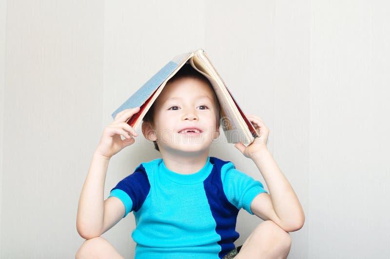 Dente de leite faltante de sorriso do menino com livro foto de stock royalty free