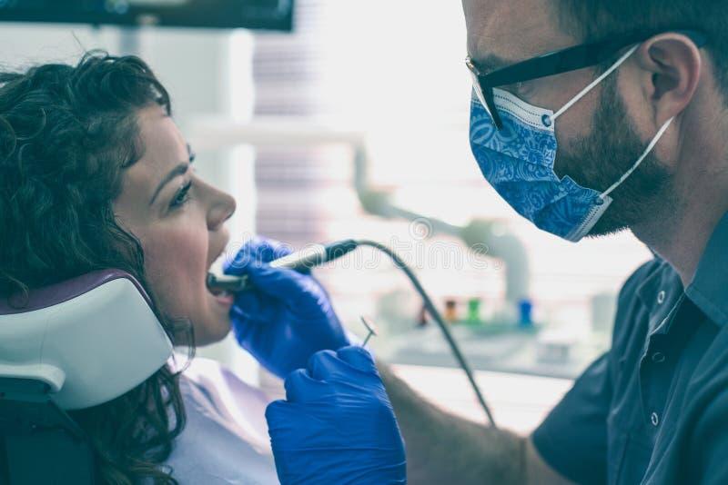 Dente dei pazienti di perforazione del dentista Dentista maschio fotografia stock