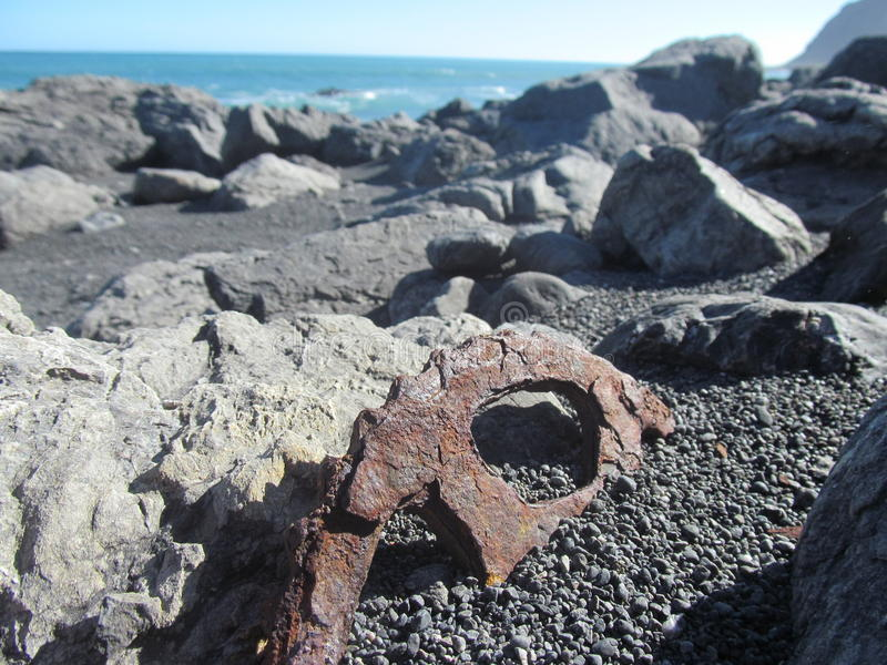 Dente/ingranaggio arrugginiti che sporge dalla spiaggia fotografia stock