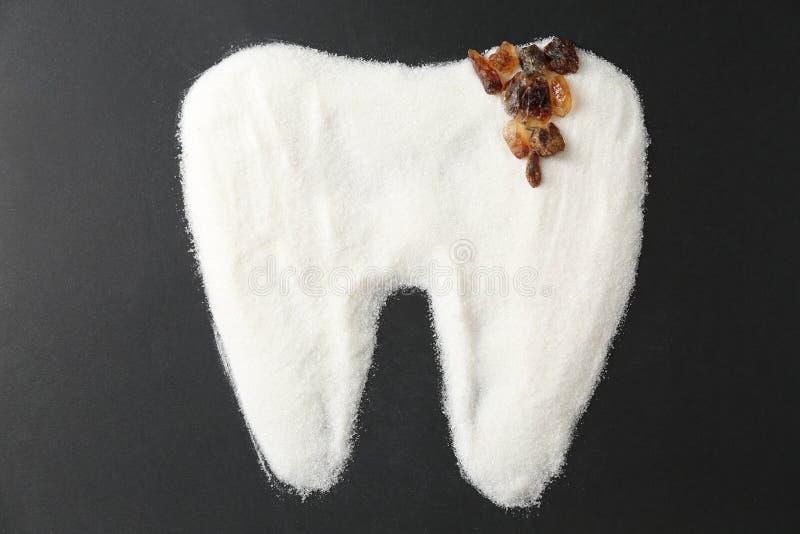 Dente molare fatto di zucchero su fondo scuro fotografia stock