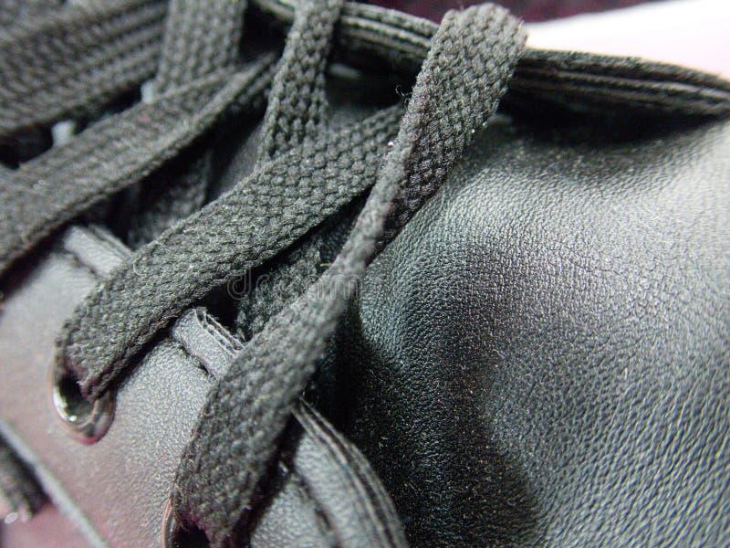 Dentelles attachées sur une chaussure foncée photos libres de droits