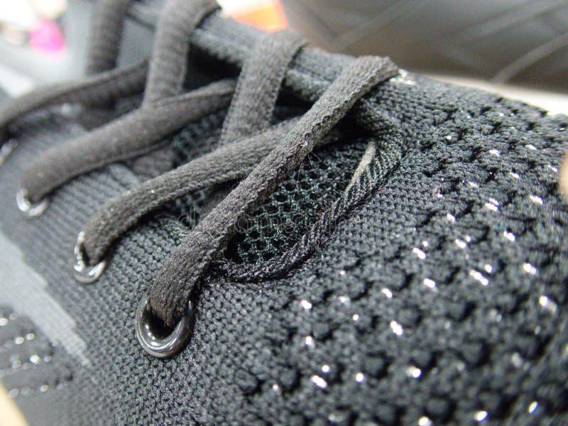 Dentelles attachées sur une chaussure foncée photo libre de droits