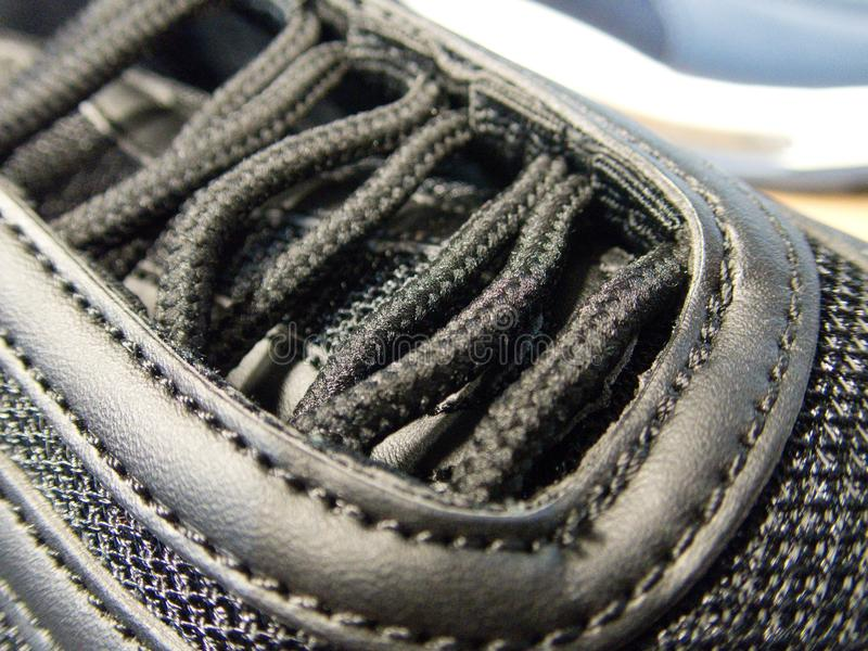 Dentelles attachées sur une chaussure foncée photos stock