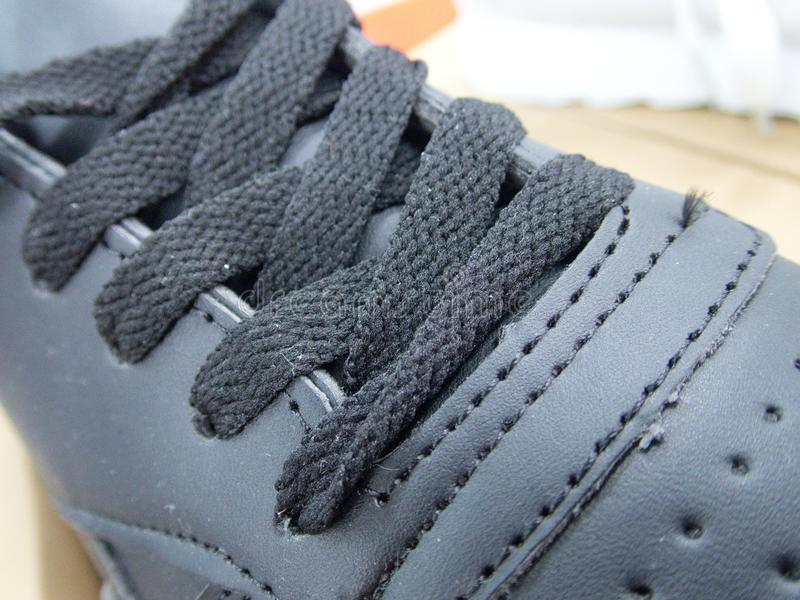 Dentelles attachées sur une chaussure foncée photographie stock libre de droits