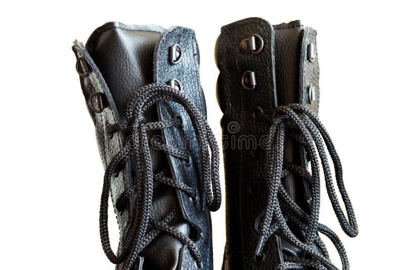 Dentelles dans les bottes noires d'armée en gros plan sur le fond blanc image libre de droits