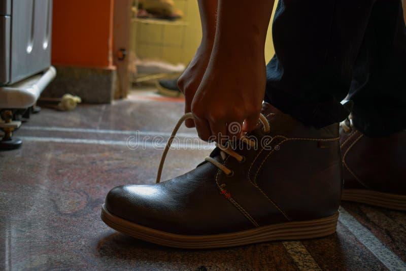 Dentelles tiding modèles de ses bottes brunes de couleur photos libres de droits