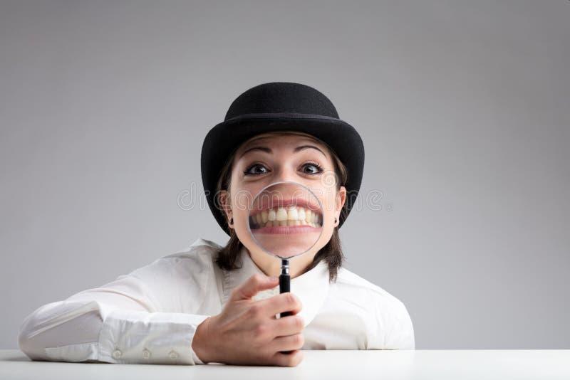 Dentes atrás de uma lente de aumento e de uma cara engraçada fotografia de stock