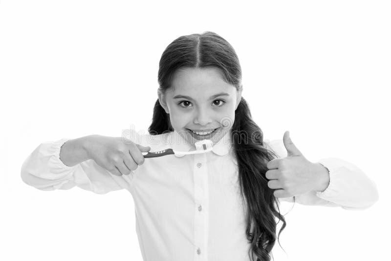 Dentes da escova cada dia Conceito da higiene oral Polegares da escova de dentes e da mostra da posse da menina acima do fundo br imagem de stock