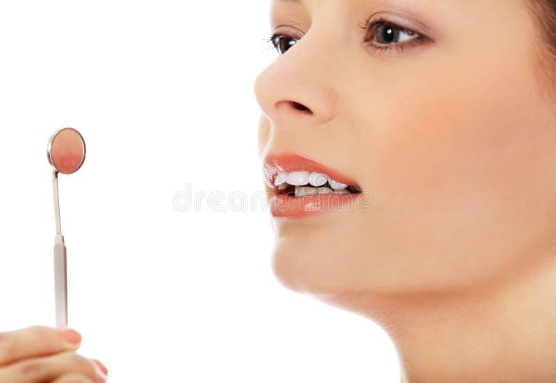 Dentes da jovem mulher e um espelho de boca do dentista foto de stock