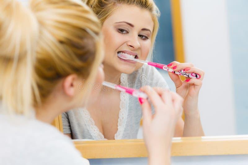 Dentes da limpeza de escovadela da mulher no banheiro fotos de stock royalty free
