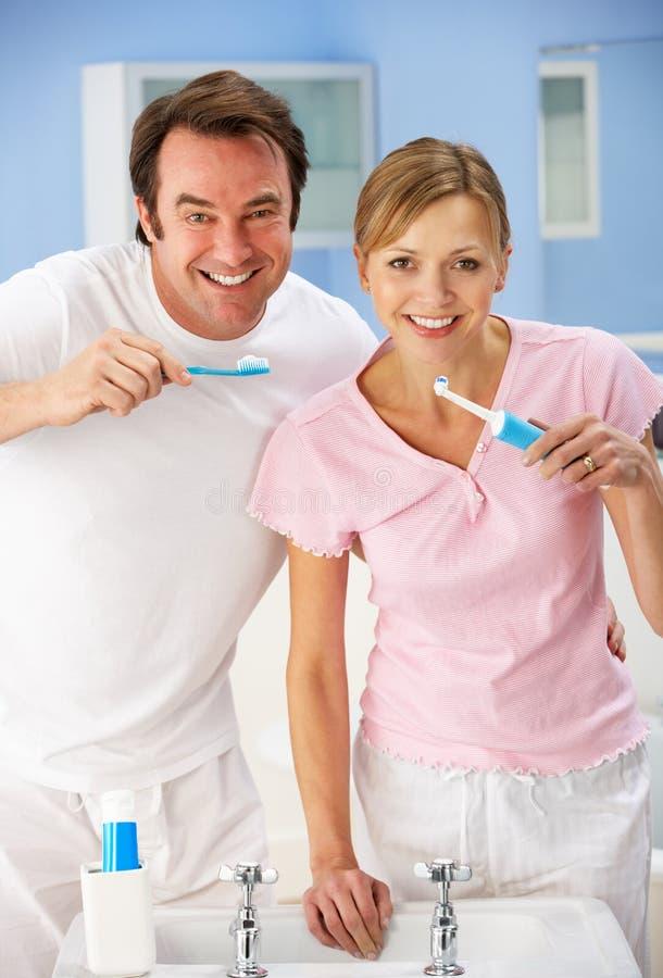 Dentes da limpeza dos pares junto no banheiro foto de stock royalty free